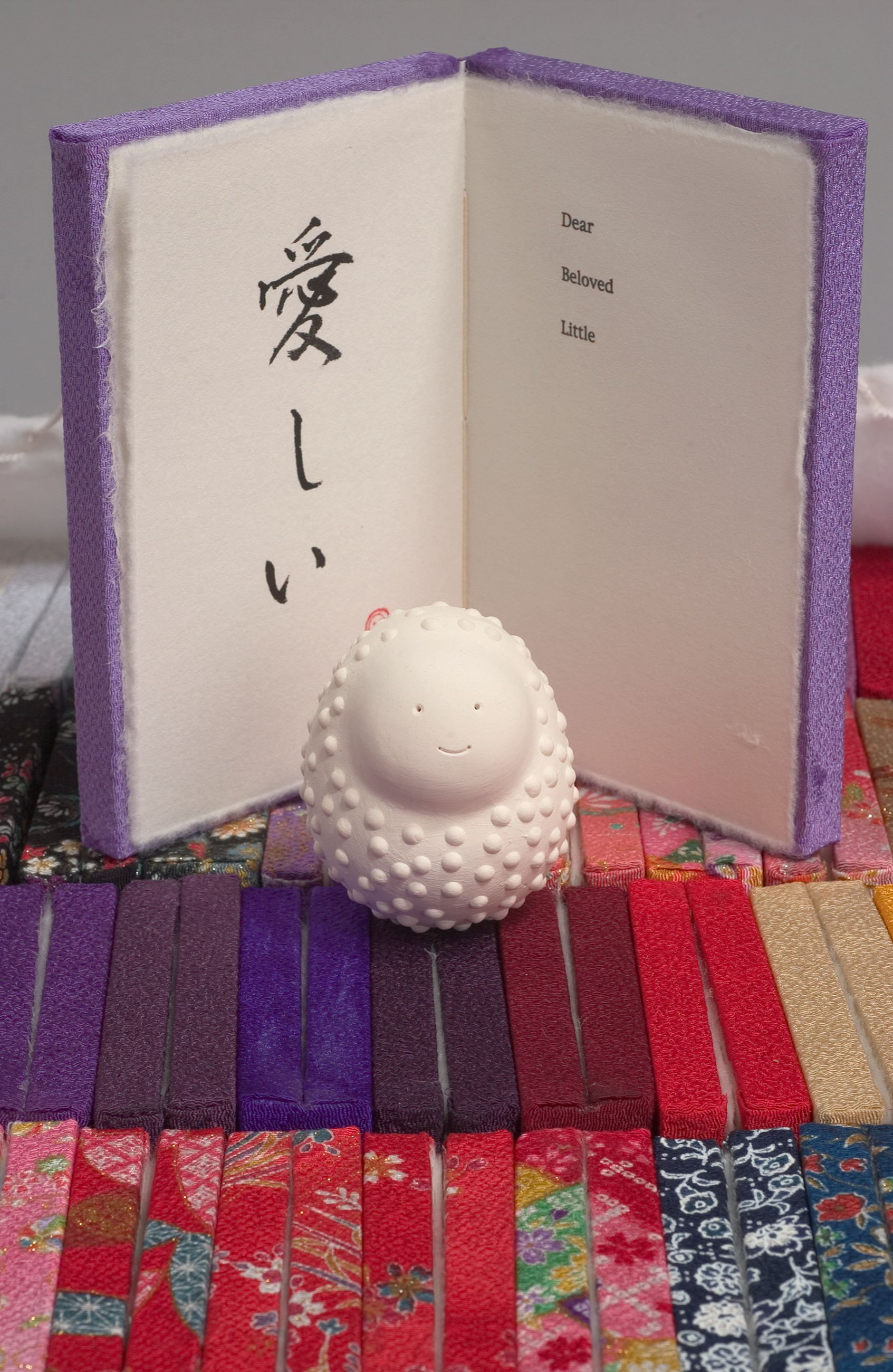 Image of Maegawa's hand made book, open with Daruma doll in front