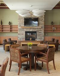 A large room with tables, chairs, and a stone fireplace.
