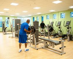 man lifting weights in the fitness room at hillcrest heights community center