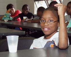 a smiling boy with glasses sitting at table with cup in front of him