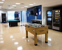 foosball and pool tables in a well lit game room with a vending machine