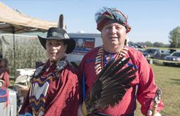 American Indian couple wearing traditional outfits while holding a bird wing.