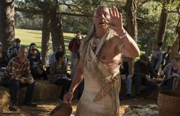 American Indian man wearing traditional clothing with his hand raised.