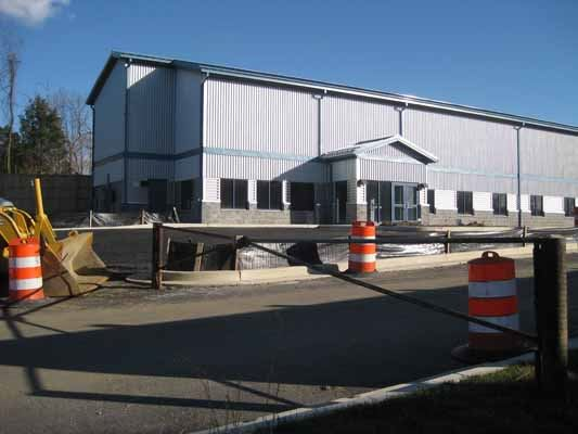 Metal building with parking lot and construction barrels in front